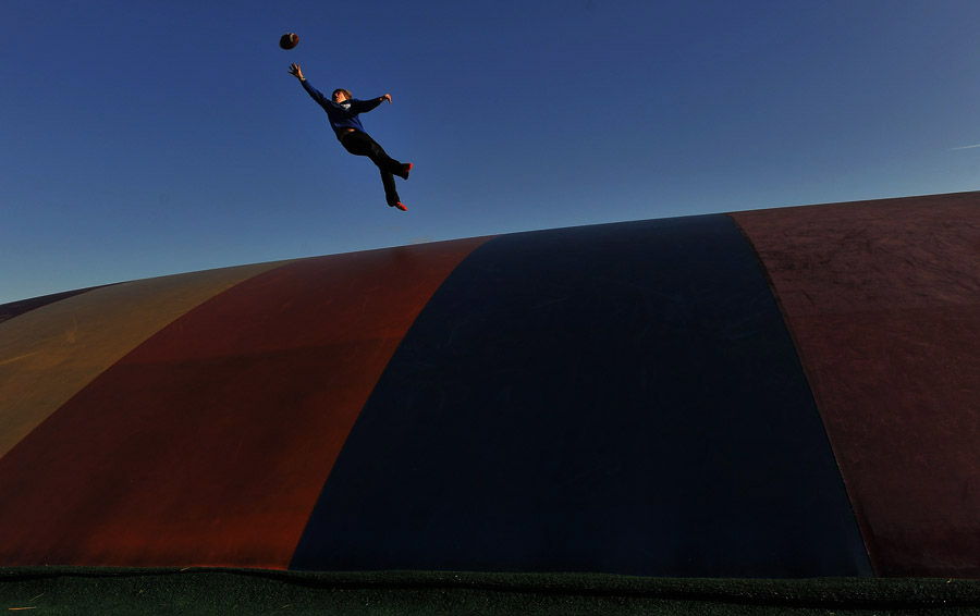 Owen Marino, 12, of Arlington, VA stretches out to catch a football as he plays on {quote}The Jumping Pillow{quote} at Ticonderoga Farms on Sunday November 25, 2012 in Chantilly, VA.  The farm has over 4,000 trees that can be picked out and cut.  (Photo by Matt McClain for The Washington Post)