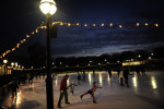 As  the last light of the day fades away, families skate at the National Gallery Sculpture Garden and Ice Rink on December 21 in Washington, DC. (Photo by Matt McClain For The Washington Post)