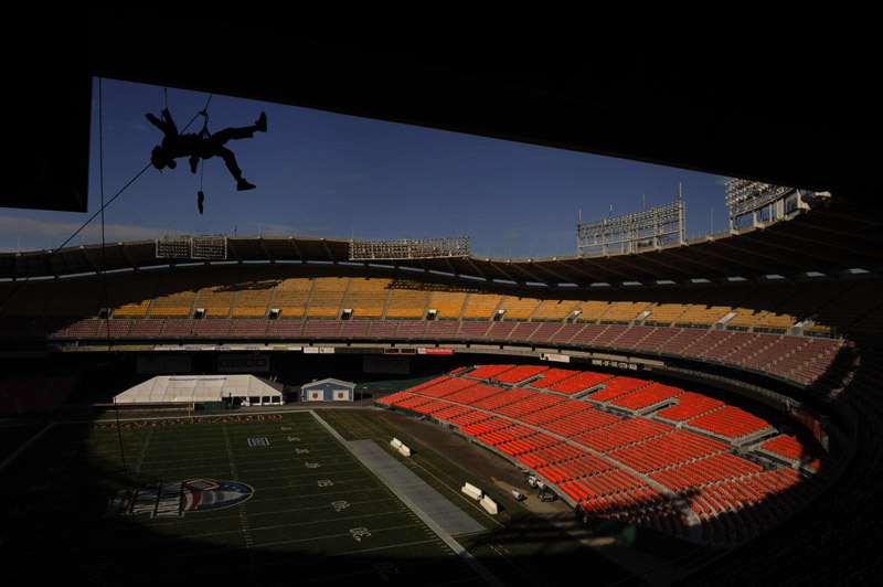 Dangling in the air, Preston McCann of Infinity Signs and Graphics repels as works on attaching signage on December 28 at Robert F. Kennedy Memorial Stadium in Washington DC in preparation for Wednesday's Military Bowl that features Maryland and East Carolina.  (Photo by Matt McClain/The Washington Post)