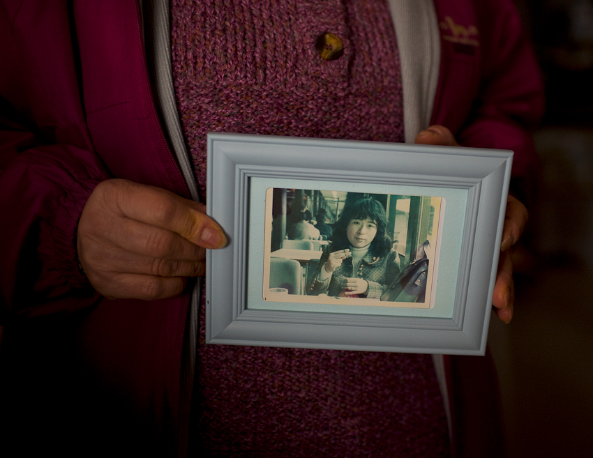 Tokiko Kitazaki, an evacuee from Tomioka-machi, Fukushima, a mushroom and rice farmer a good portion of her life and mother of two, holds an old photograph of herself when she was 25 years old. {quote}Life is different now, things will never be the same,{quote} she says. Tomioka evacuee houses, Koriyama, Japan. Feb. 2014