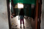 A young asylum-seeker stands behind a curtain at the entrance of a one room apartment inside a low income building on the outskirts of Bangkok. Mar. 2015