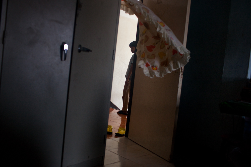 A young boy stands in the hallway of the building where he lives. Most people don't go far, unless they are footsteps away from the premises, in fear of being arrested and detained inside the Immigration Detention Center in Bangkok. Apr. 2015