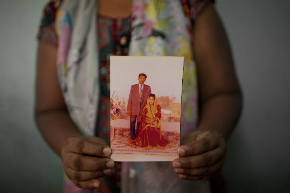 An asylum-seeker from Lahorre, Pakistan, holds a wedding photo of herself when she was younger. She and her two sons have been living in the same room since late 2013. Her brother is currently detained inside the Immigration Detention Center in Bangkok for having an expired visa. They wait for their next visa application interview. Mar. 2015