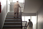 Two men walk the stairwell in one of the main buildings that house hundreds of asylum-seekers, mostly from Pakistan, Somalia and Sri Lanka. Mar. 2015