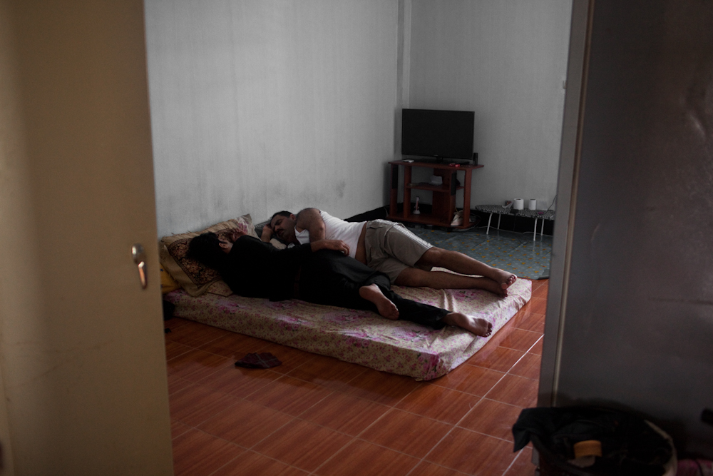 Asylum-seekers sleep in their one room apartment as there is very little socializing or entertainment going on. They mostly stay inside the building in fear of being arrested on the streets by immigration police for not having legal status in Thailand. Apr. 2015