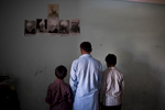 A father and his two sons from Islamabad, Pakistan, seeking asylum, practice their faith inside their room. They are Ahmadi Muslims, a religious minority, who is often targeted and discriminated against by other Muslims in Pakistan. Apr. 2015