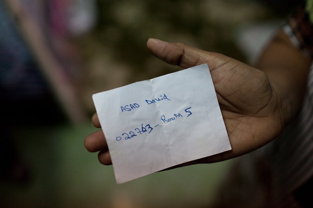 Sakeena, an asylum-seeker from Lahore, Pakistan, holds a note with information about her son who is being held at the Immigration Detention Center in Bangkok. Asad, 22,  was arrested for having an expired visa outside of a nearby seven eleven store on the outskirts of Bangkok. He has been detained for 5 months inside the Immigration Detention Center. Sakeena and her husband wait patiently inside their room hoping to receive any news regarding their son. Mar. 2015
