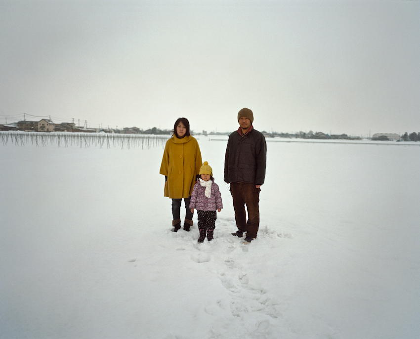 Nozaki and his family stand for a portrait in a snow covered vegetable field in the town of Aizuwakamatsu, Fukushima Prefecture. Nozaki and his wife are not overly concerned about radiation contaminating food and water, but how discrimination will impact the future for their 4 year-old daughter. Feb. 2014