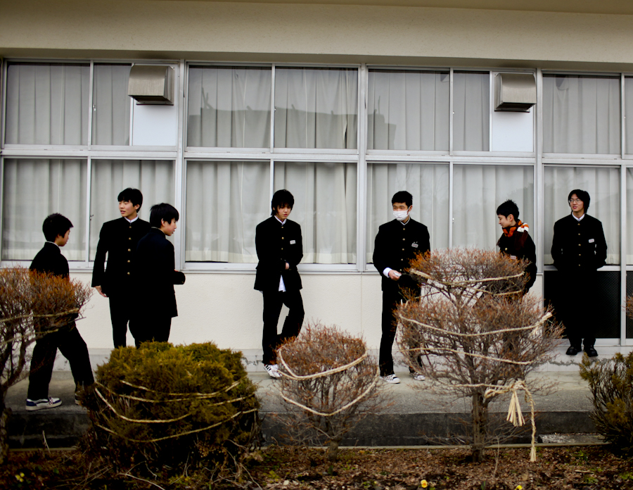 Students hang out in front of a Junior High School after graduation in the Onuma disctrict of Aizumisato, Fukushima Prefecture. There is a constant fear among young parents throughout Fukushima that the government is not providing truthful information about high levels of radiation. Another concern is discrimination against their child in the future. Mar. 2014