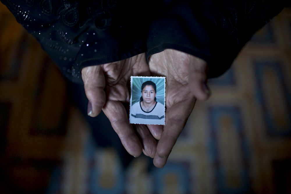 Fayza, holds a picture of her youngest daughter, Nashwa, at the age of 12, home in Zakazik, Egypt. Nashwa, now 20, was abducted walking near Tahrir Square, July of 2011, by a military officer who forced her to go with him where she was held against her will for two days. Nashwa was able to escape and return home, within an hour, the military bombarded her home and she was taken to a military prison. There is chance she can serve up to 10 years in prison. Egypt. Mar. 18, 2012