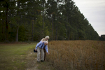 Chris and her father inspect a dried out soy bean patch near the his childhood home, after spending the day with family. Varnville, SC. Nov. 2014