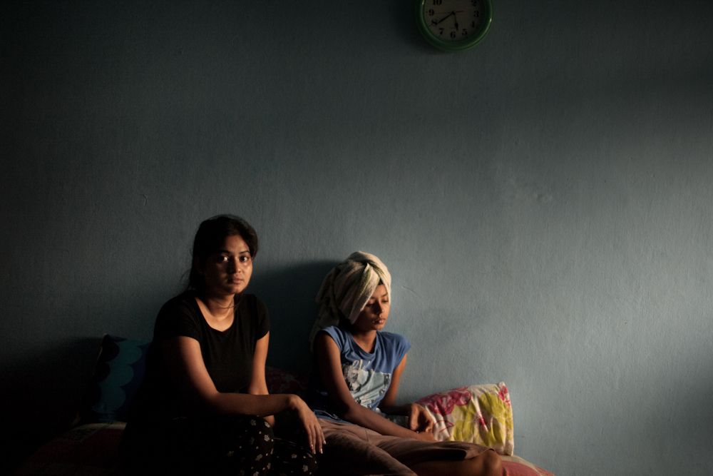 Donia, and her younger sister Azeeka, from Karachi Pakistan sit in their room. After receiving constant death threats by local extremist groups targeting Christians in Karachi, their family decided to sell everything and leave. They have been seeking asylum in Bangkok for almost a year and a half. They stay in their room most of the day and usually don't leave the premises in fear of being arrested by immigration police and detained inside the IDC for not having a valid visa. They wait for their visa application interview. Mar. 2015