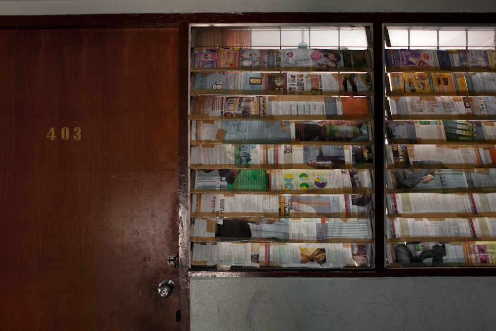 A window of a one room apartment covered by magazine pages inside one of the main buildings that house hundreds of asylum-seekers, mostly from Pakistan, Somalia and Sri Lanka. Mar. 2015
