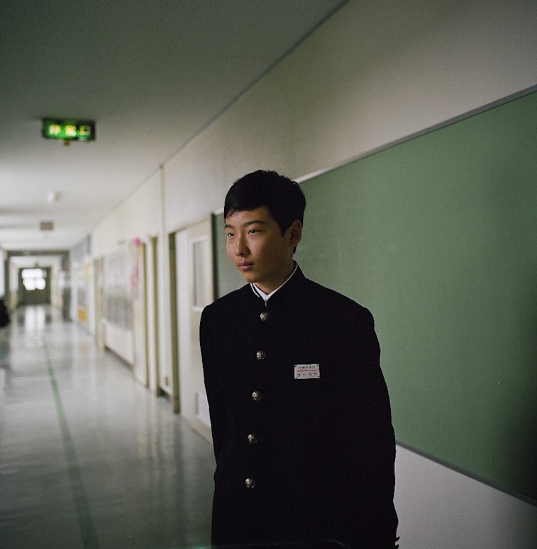 A young student stands for a portrait at a Junior High School after graduation in the district of Aizu. There is a constant fear among young parents in Fukushima that the government is not providing important information about hotspots of radiation. Another major concern among young families is discrimination, and how it will impact their child's life in the future. Mar. 2014