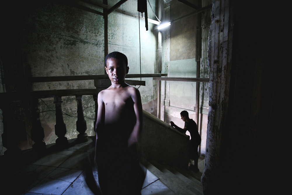 A young boy stands for a portait in a dilapidated apartment buildning in Havana, Cuba. 2009