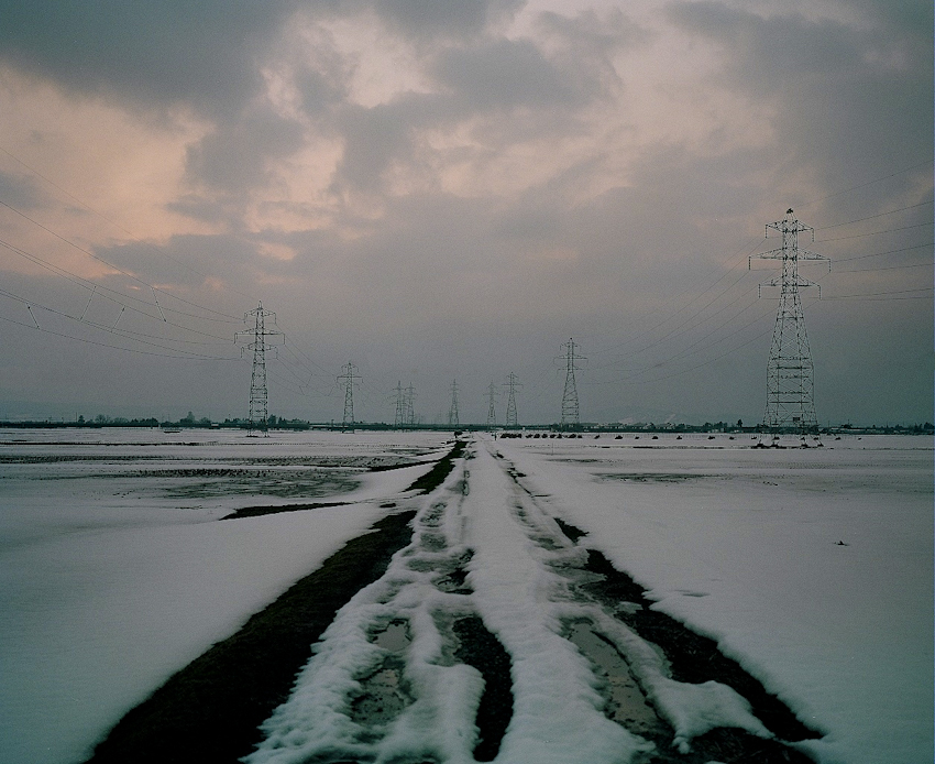 Electric towers line the landscape of a snow covered sea of rice fields outside of Koriyama City, Fukushima Prefecture. Residents fear the food chain is contaminated due to the onshore wind patterns that create hotspots of radiation in the mountains where rain water finds its way down to rice and vegetable fields throughout Fukushima, Japan. Mar. 2014