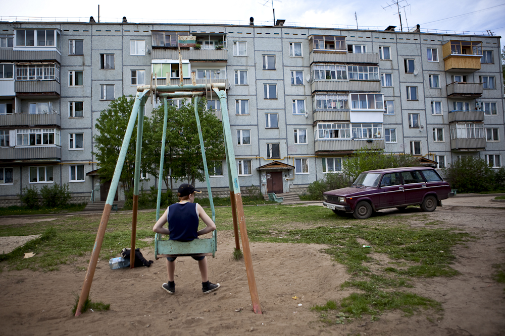 A young boy rests on a swing outside of his apartment house in Zaton, Russia.
