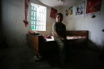 Standing about a metre tall, Mai Thi, 28, Agent Orange victim, patiently waits for her mothers return to comfort her in the bedroom of their home in the Kim Dong district of Nhat Tan, Vietnam.
