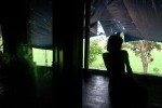 Le Sinh, 14, Agent Orange victim, looking out from the lanai at home in the Benh Vien district, Da Nang Vietnam.