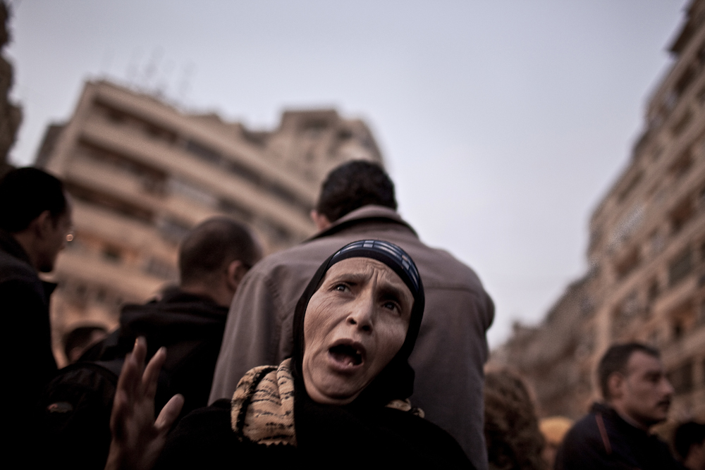 An Egyptian woman chants anti-goverment slogans as protesters gather around awaiting an evening of demonstrations in Tahrir Square. Cairo, Tuesday, Feb. 8, 2011