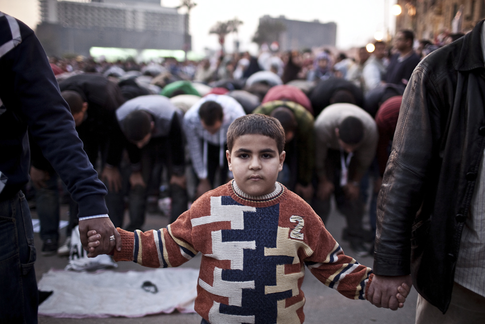 A young Egyptian protester takes part in securing  prayers at Tahrir Square in Cairo.Tuesday, February 8, 2011