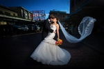 A gust of wind catches the veil as the bride & groom kiss at the Pike Place Market prior to their wedding at the Seattle Aquarium. (Wedding Photography by Scott Eklund/Red Box Pictures)