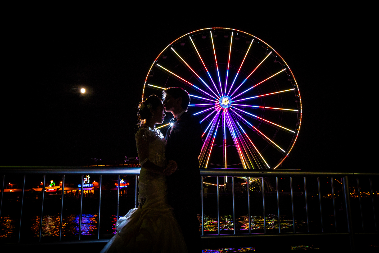 The bride & groom kiss in front of the Great Seattle Wheel on the Seattle waterfront during their wedding at the Seattle Aquarium. (Wedding Photography by Scott Eklund - Red Box Pictures)