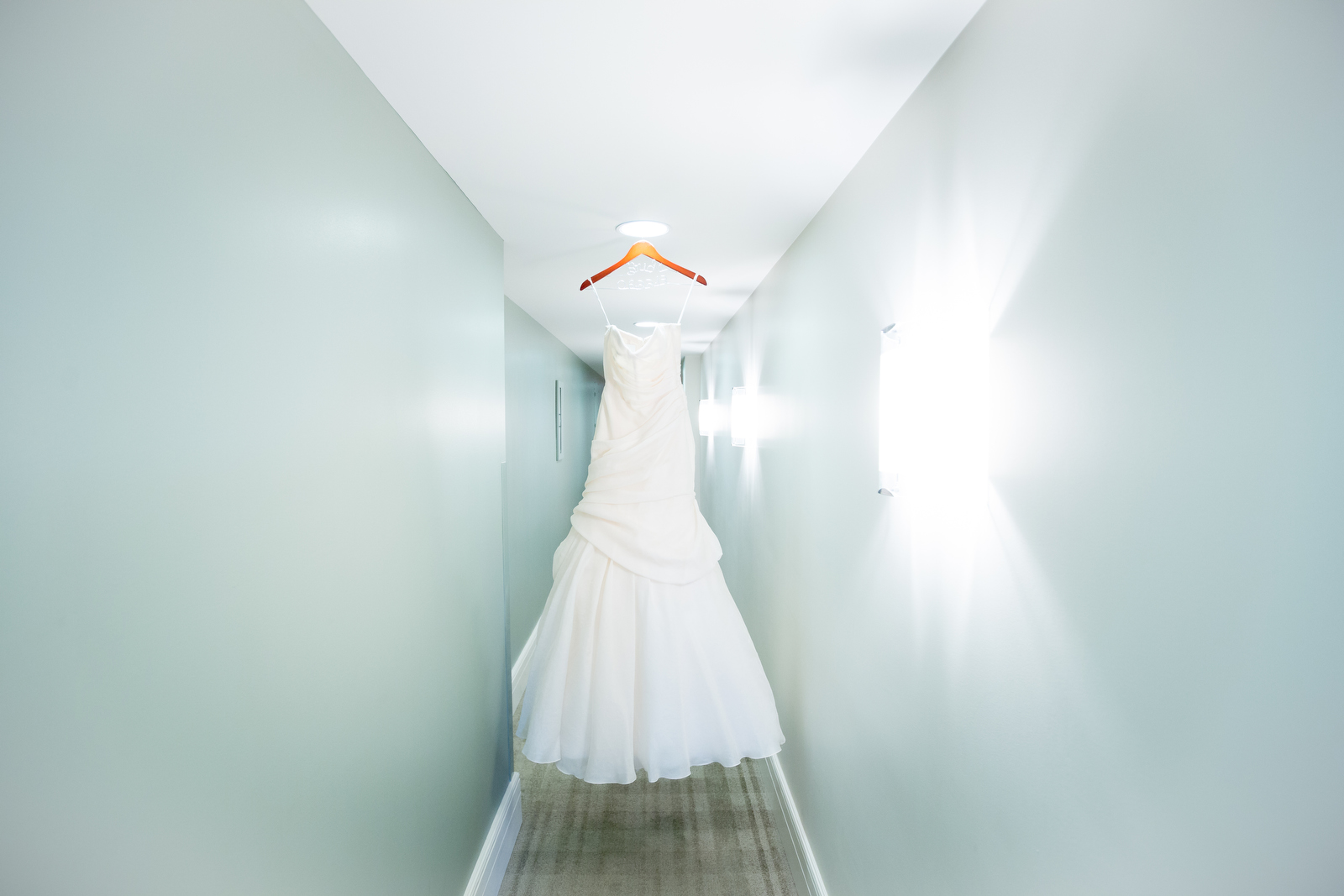 The bride's wedding dress hangs at the Washington Athletic Club (WAC) prior to the start of the wedding at the Seattle Aquarium. (Wedding Photography by Scott Eklund/Red Box Pictures)