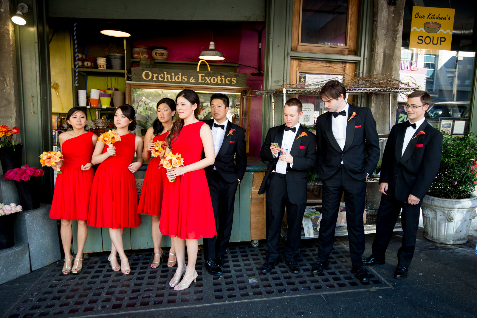 The bridal party hangs out at the Pike Place Market in Seattle prior to the start of the wedding at the Seattle Aquarium. (Wedding Photography by Scott Eklund - Red Box Pictures)