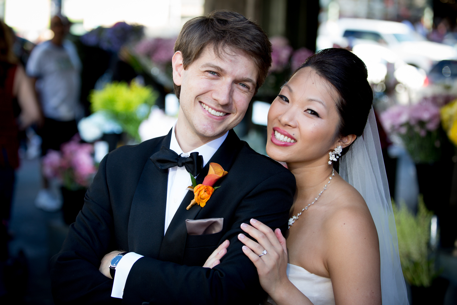 The bride and groom pose for a portrait at the Pike Place Market prior to their wedding at the Seattle Aquarium. (Wedding Photography by Scott Eklund - Red Box Pictures)