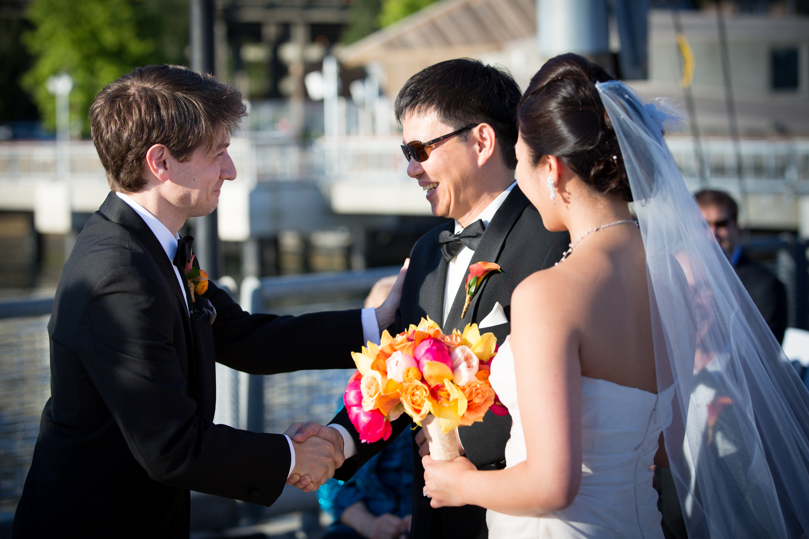 The father-of-the-bride shakes hands with the groom after he escorted the bride down the aisle during the wedding ceremony at the Seattle Aquarium. (Wedding Photography by Scott Eklund - Red Box Pictures)
