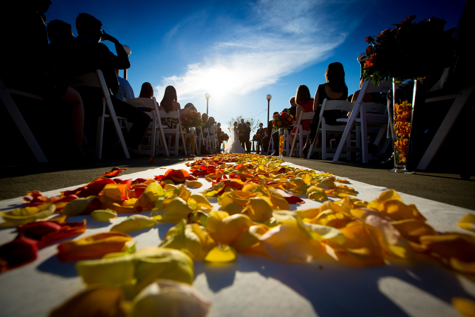 The aisle is decorated with flowers as the bride and groom exchange vows during their wedding ceremony at the Seattle Aquarium. (Wedding Photography by Scott Eklund - Red Box Pictures)