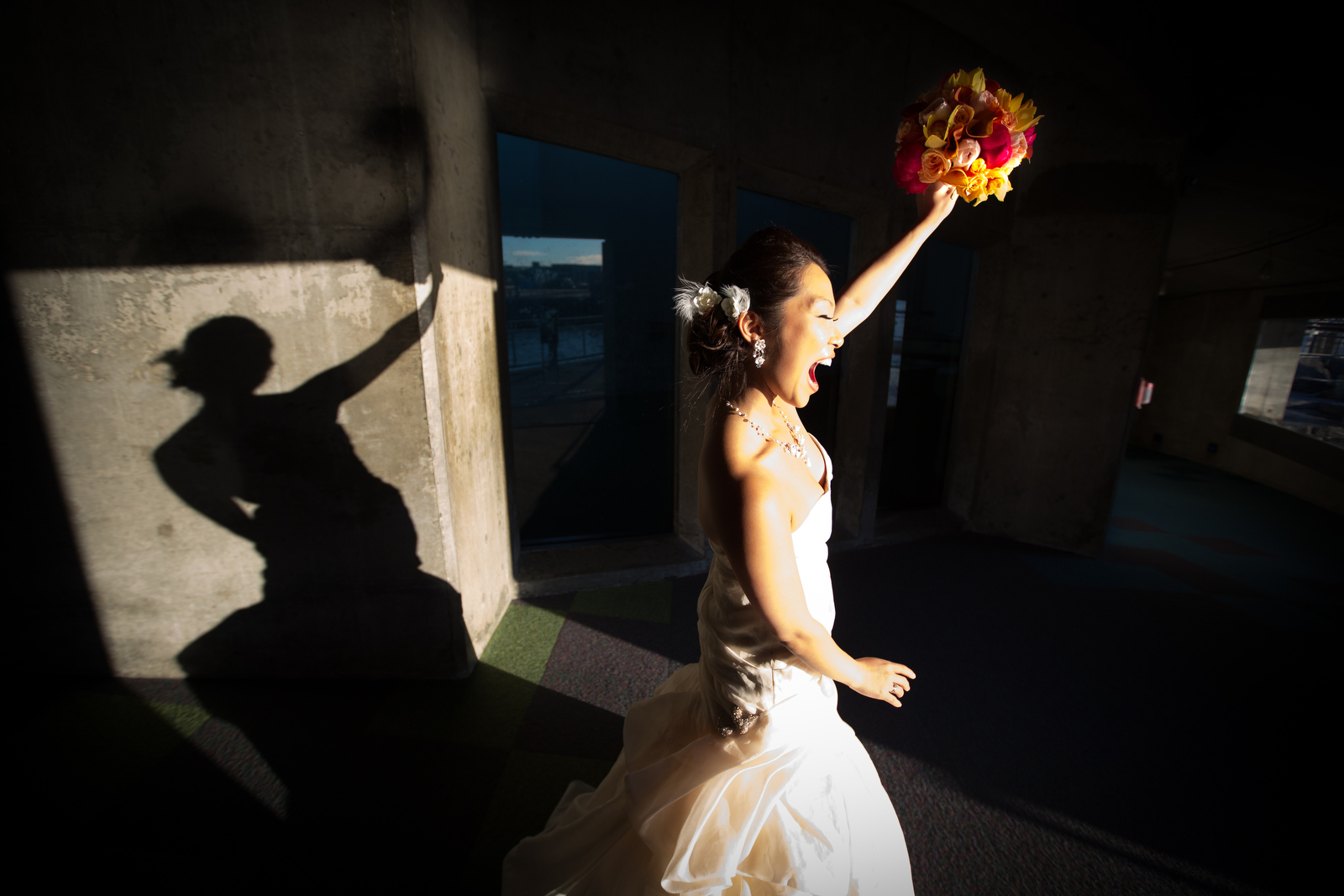 The bride raises her bouquet as she celebrates her wedding at the Seattle Aquarium. (Wedding Photography by Scott Eklund - Red Box Picures)