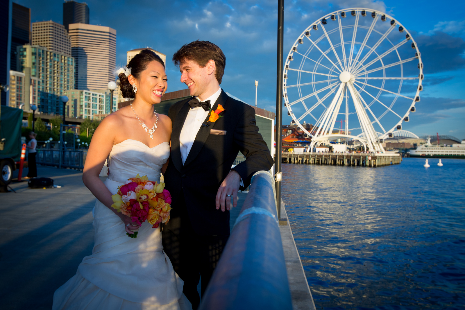 A portrait of the bride & groom in front of the Great Seattle Wheel on the waterfront during their wedding at the Seattle Aquarium. (Wedding Photography by Scott Eklund - Red Box Pictures)