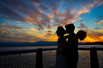 The bride & groom are silhouetted as they kiss in front of a beautiful sunset on the Seattle waterfront during their wedding at the Seattle Aquarium. (Wedding Photography by Scott Eklund - Red Box Pictures)