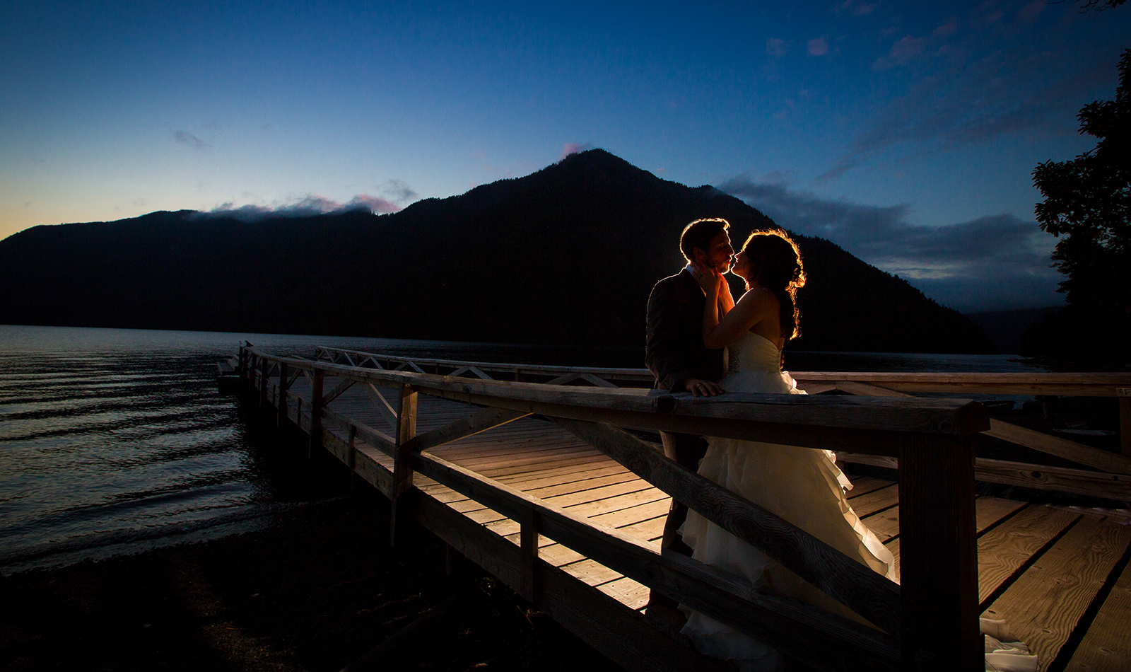 The bride and groom kiss on the dock at their Lake Crescent Lodge wedding in Port Angeles, Washington. (Wedding Photography by Scott Eklund /Red Box Pictures)