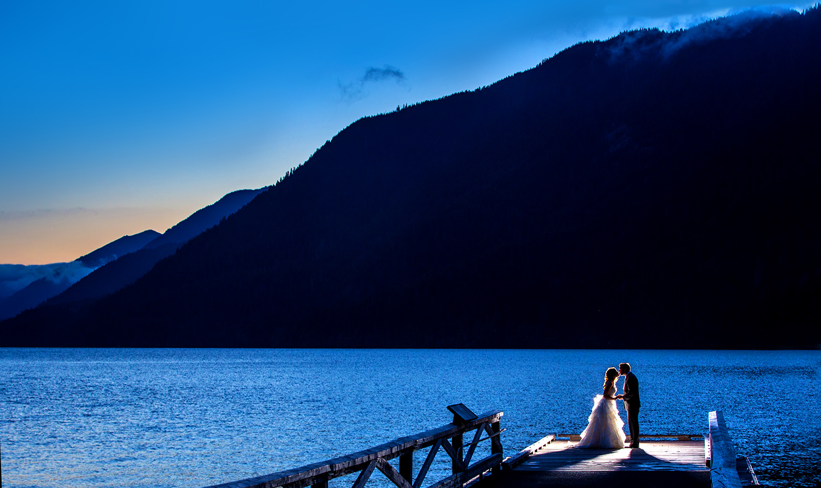 The bride & groom kiss on the dock at dusk during their Lake Crescent Lodge Wedding in Port Angeles, Washington. (Wedding Photography by Scott Eklund /Red Box Pictures)