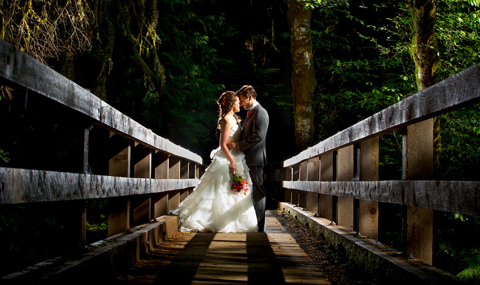 The bride and groom kiss on a bridge during their Lake Crescent Lodge Wedding in Port Angeles, Washington. (Wedding Photography by Scott Eklund /Red Box Pictures)