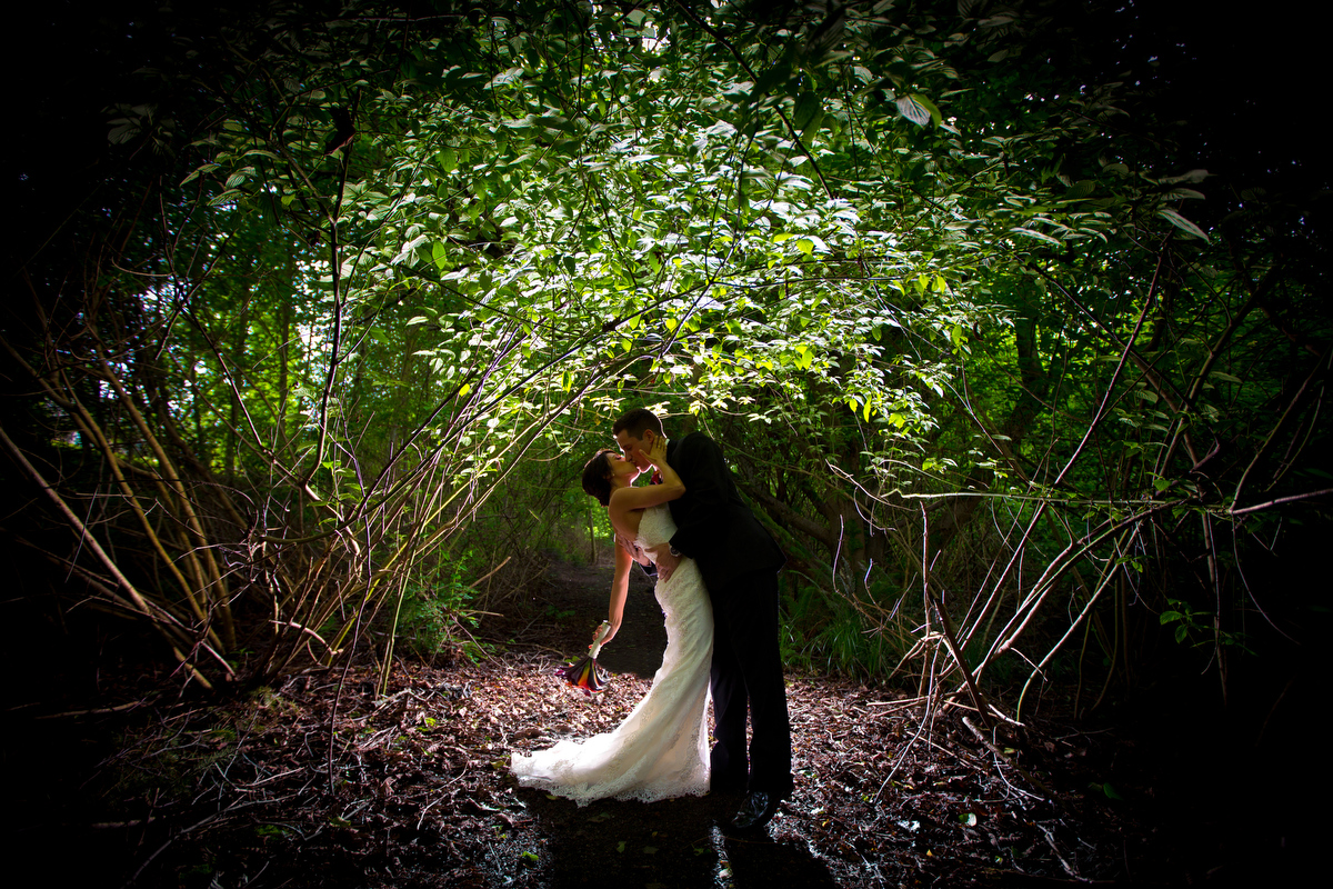 The bride and groom kiss in the woods during their  Cedarbrook Lodge wedding in Seattle, Washington. (Wedding Photography by Scott Eklund - Red Box Pictures)