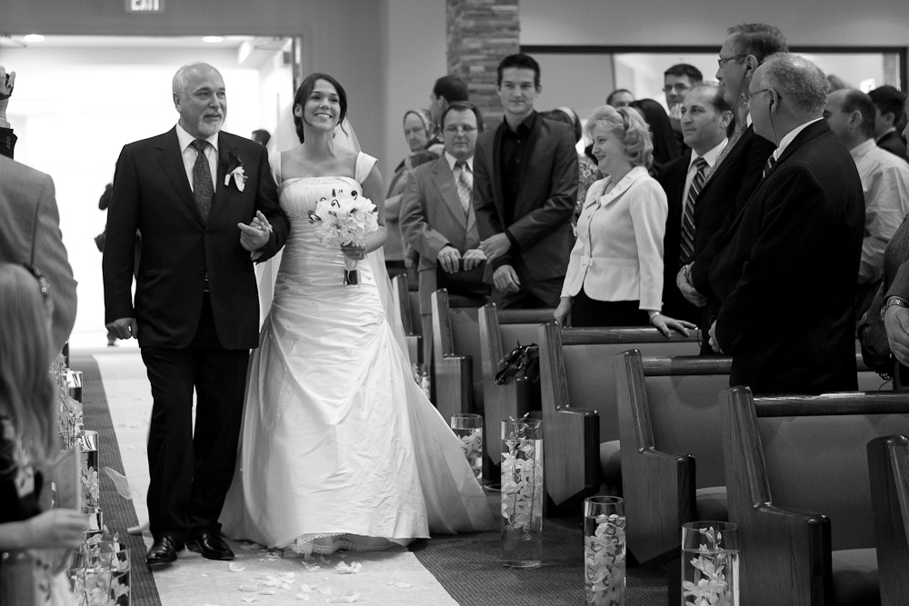 Silvia is escorted down the aisle by her father during the processional of her wedding ceremony at First Romanian Pentacostal Church in Bothell, WA. (Photo by Scott Eklund/Red Box Pictures)