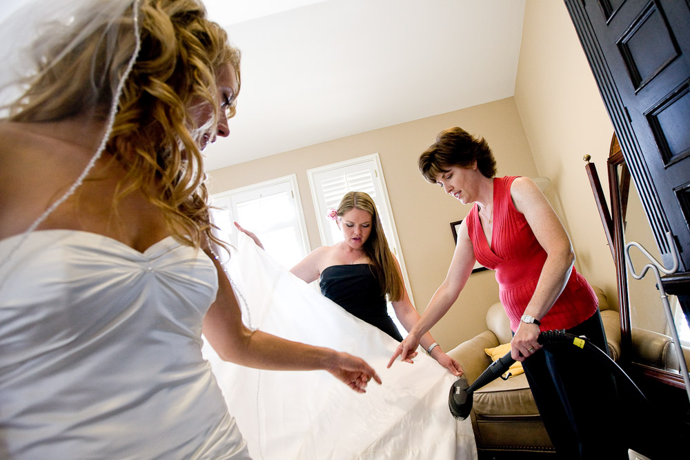 Pauline gets help getting ready from a bridesmaid as the wedding coordinator, Melissa Parker, steams the wrinkles out of the wedding dress before the start of her wedding at the Golf Club at Newcastle near Seattle. (Wedding Photography by Scott Eklund/Red Box Pictures)