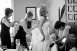 Bride Pauline gets help getting ready from her mom and a bridesmaid as the wedding coordinator steams the wrinkles out of the wedding dress before the start of the wedding at the Golf Club at Newcastle near Seattle. (Wedding Photography by Scott Eklund/Red Box Pictures)