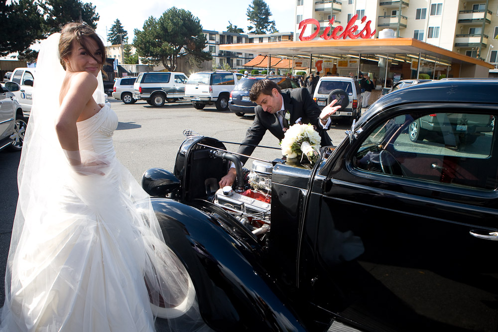 Adrian pretends to inspect the engine of a hot rod parked at Dick's Drive-in in Seattle when they arrived to eat hamburgers prior to their wedding ceremony. (Photo by Scott Eklund/Red Box Pictures)