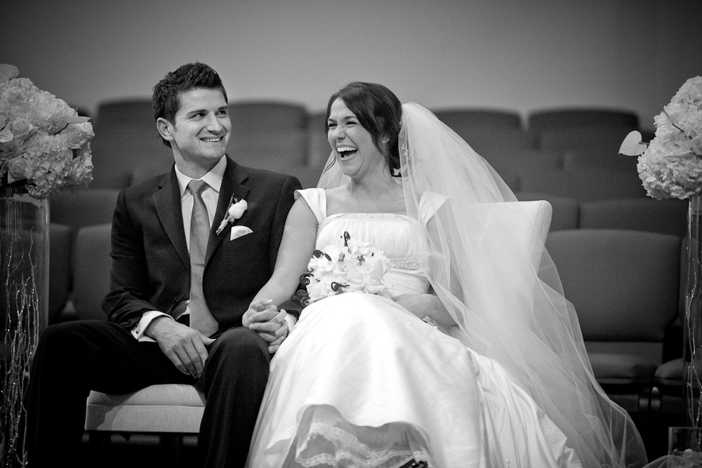 Silvia and Adrian hold hands and laugh at comments made during their wedding ceremony at First Romanian Pentacostal Church in Bothell, WA. (Photo by Scott Eklund/Red Box Pictures)