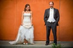 Michelle & Matt have their portrait taken in front of an orange stucco wall near their wedding venue at The Attic in Sumner, WA. (Photography by Scott Eklund/Red Box Pictures)