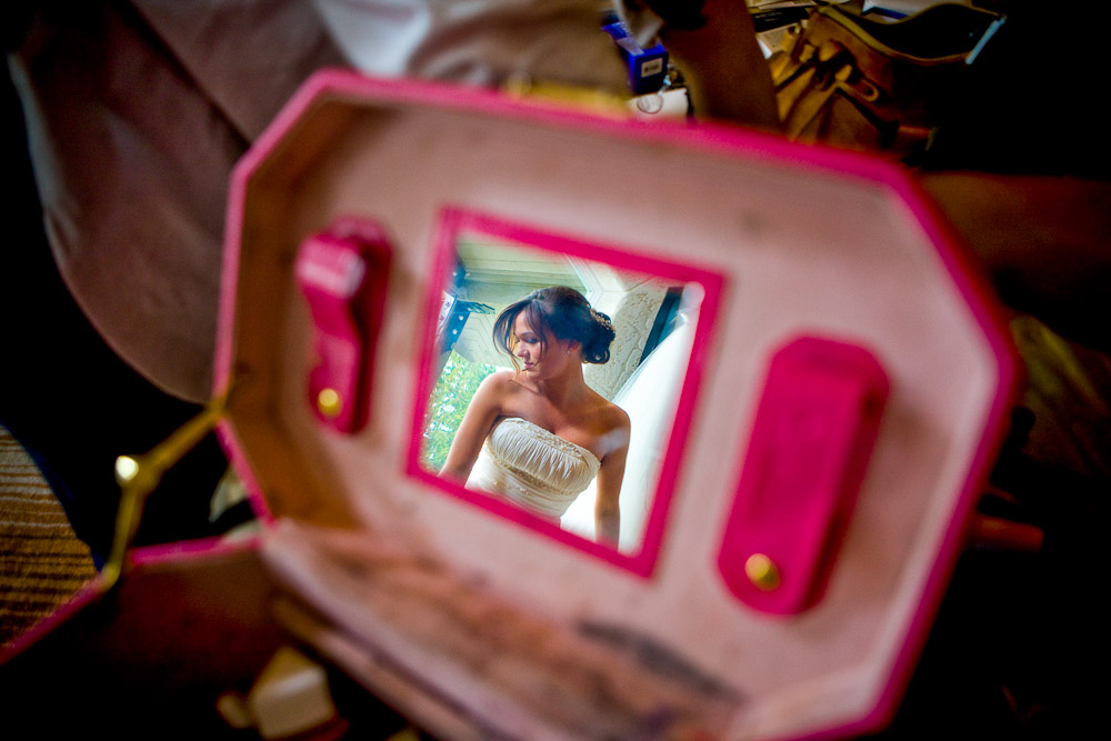 Wearing her wedding dress, Silvia is reflected in the mirror of a makeup case as she finishes getting ready for her wedding at her home in Bothell, WA. (Photo by Scott Eklund/Red Box Pictures)