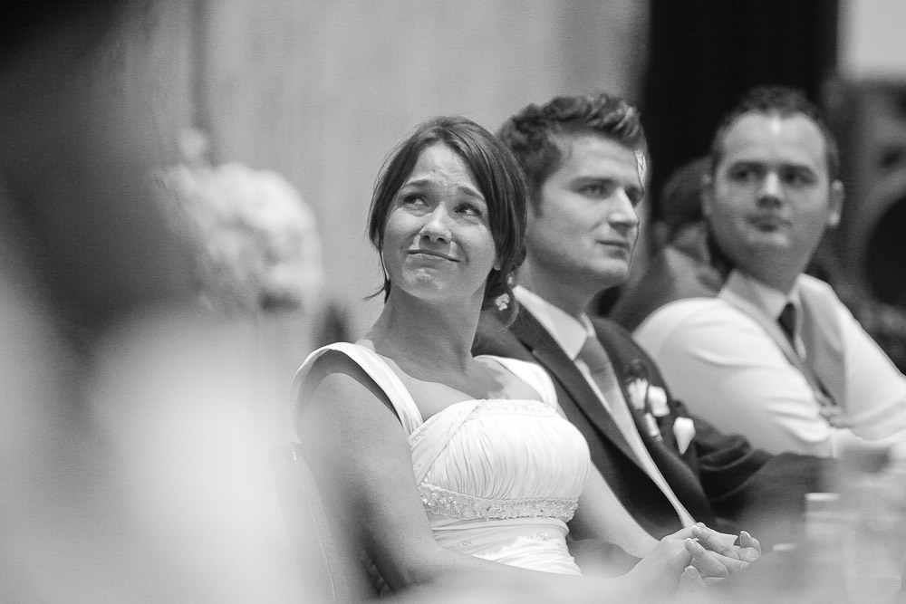Silvia weeps and smiles as she listens to her brother give a toast during their wedding reception at the Hyatt Regency in Bellevue, WA. (Photo by Andy Rogers/Red Box Pictures)