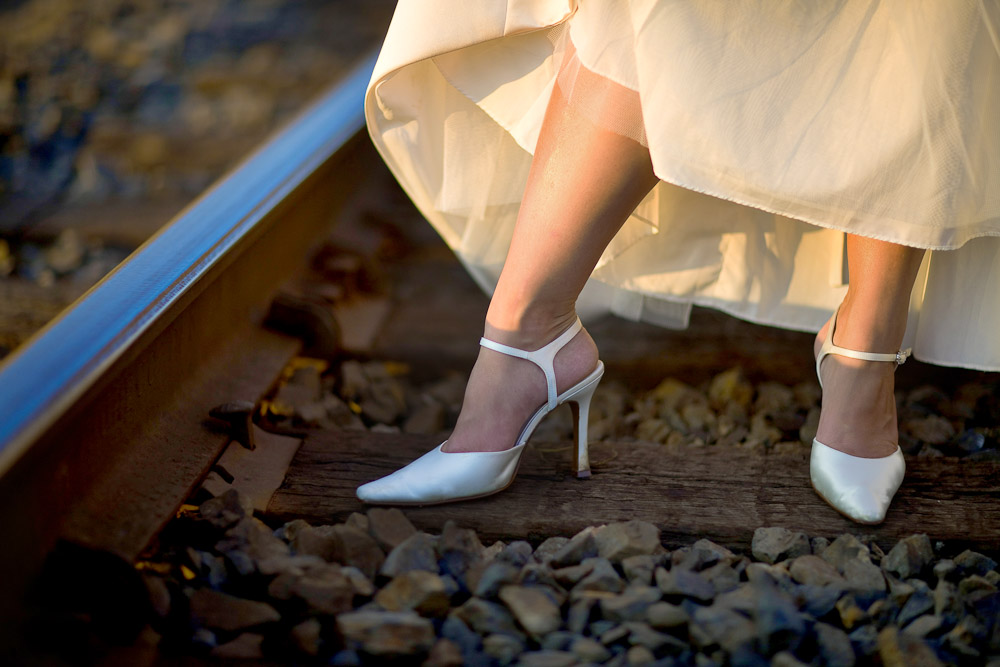 Michelle shows off her fancy white shoes as the bride walks along the railroad tracks in Sumner, Washington after her wedding at The Attic. (Photography by Scott Eklund/Red Box Pictures)