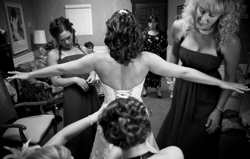 The corset is tied on the back of Michelle's wedding dress by her bridesmaids at The Attic in Sumner, WA. (Photo by Scott Eklund/Red Box Pictures)