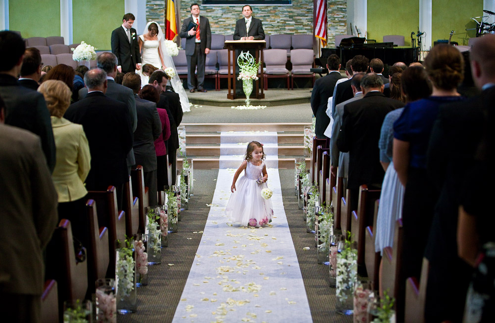 A flower girl walks down the aisle to her seat at the start of Silvia and Adrian's wedding ceremony at First Romanian Pentacostal Church in Bothell, WA. (Photo by Andy Rogers/Red Box Pictures)